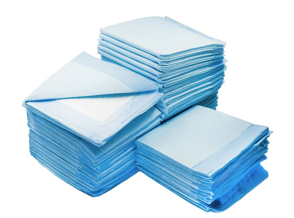 Image of stacks of potty pads for how to potty train a dog